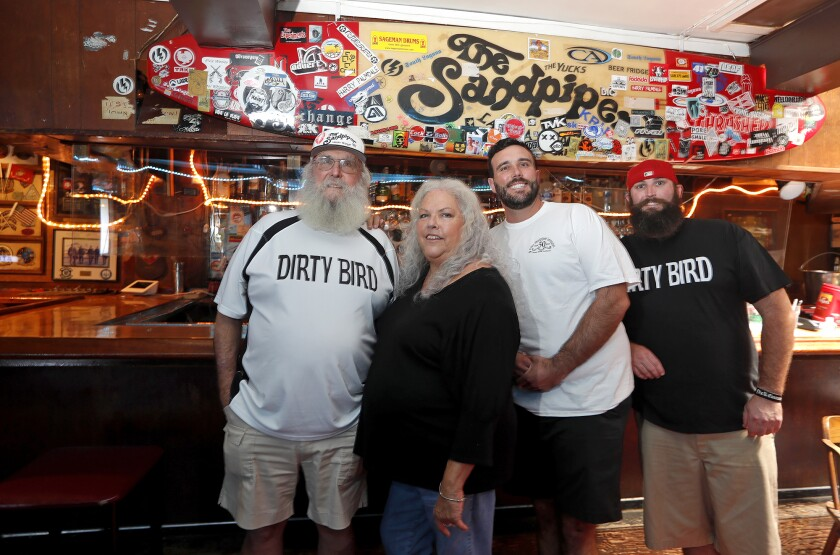 Owners Chuck and Jeannie Harrell, with their sons Spencer and Grant at the Sandpiper Lounge.