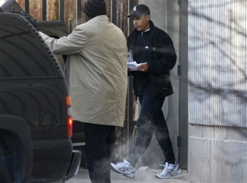 President-elect Barack Obama, wearing a Chicago White Sox baseball cap, leaves a gym and walks towards his vehicle in Chicago, Friday, Dec. 5, 2008. (AP Photo/Charles Dharapak)