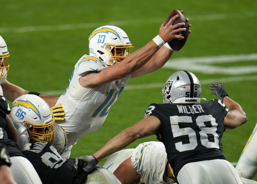 Chargers quarterback Justin Herbert scores the game-winning touchdown in overtime against the Las Vegas Raiders.