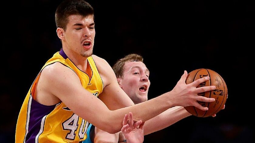Lakers center Ivica Zubac, pulling down a rebound over Hornets center Cody Zeller during a game on Feb. 28, will be under the watchful eye of management as he works on his game this summer.