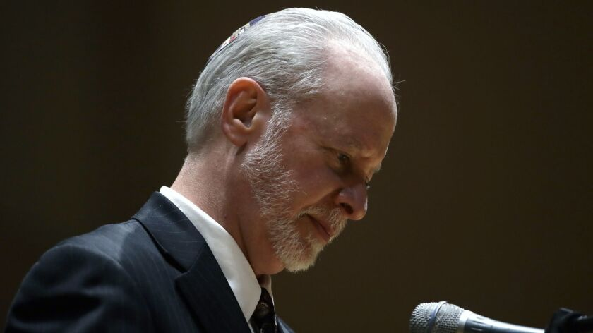 Rabbi Jeffrey Myers stands at the podium during a community gathering held in the aftermath of Saturday's deadly shooting at the Tree of Life Synagogue in Pittsburgh on Sunday.