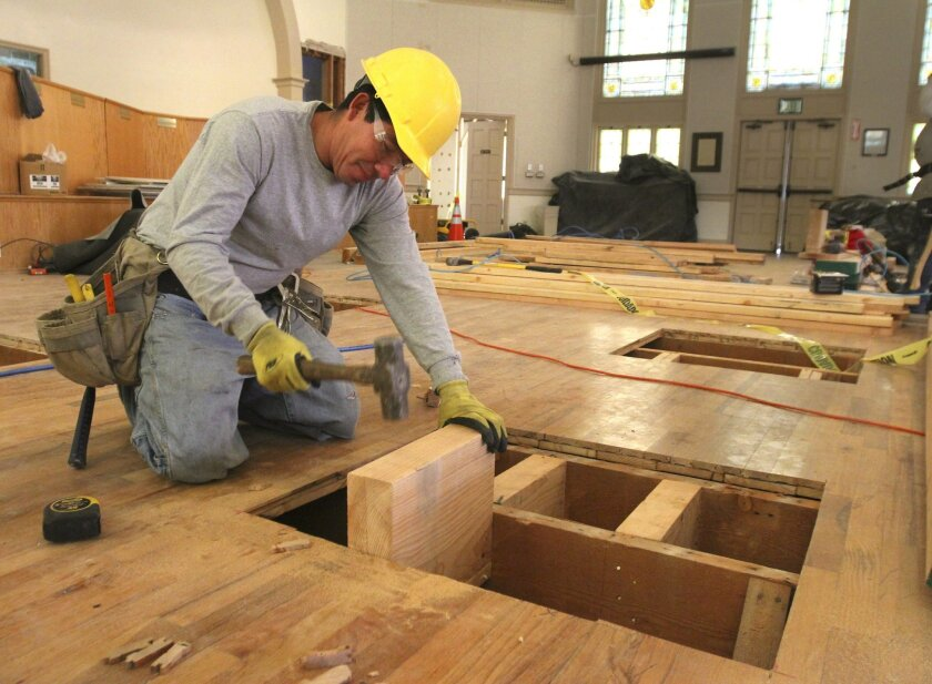 Cruz Sanabria hammers a piece of wood into the flooring of the Lake Elsinore Cultural Center as he readies it for wall bracings during the seismic retrofit of the building.