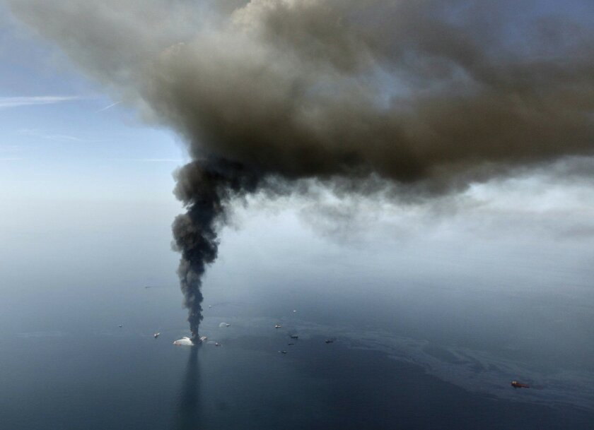 FILE - In this April 21, 2010 file photo by Gerald Herbert, the Deepwater Horizon oil rig burns in the Gulf of Mexico. Rig fires happen with some regularity, but when word came that the rig was listing badly after an explosion the night before, New Orleans-based Herbert raced to a small airport and