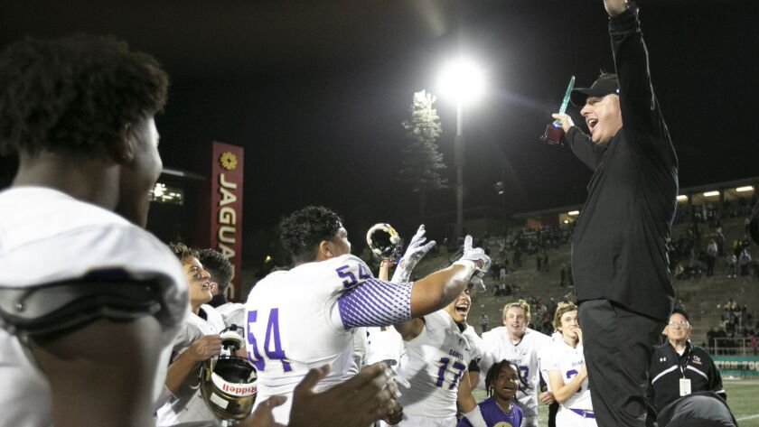 Saints coach Joe Kremer shares the trophy with his team after St. Augustine defeated Helix in overtime.