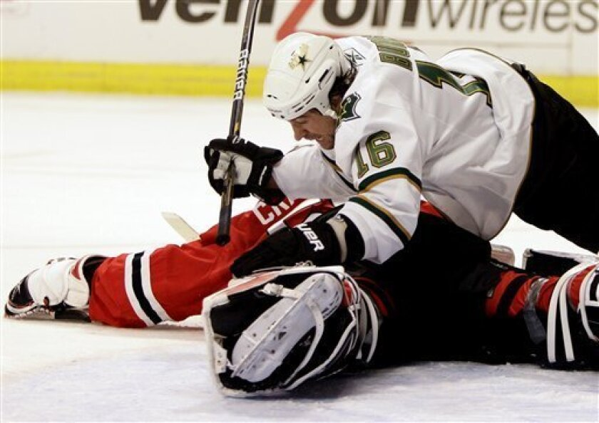 Dallas Stars' Adam Burish (16) slides into Chicago Blackhawks goalie Corey Crawford during the first period of an NHL hockey game in Chicago, Wednesday, Jan. 5, 2011. (AP Photo/Nam Y. Huh)