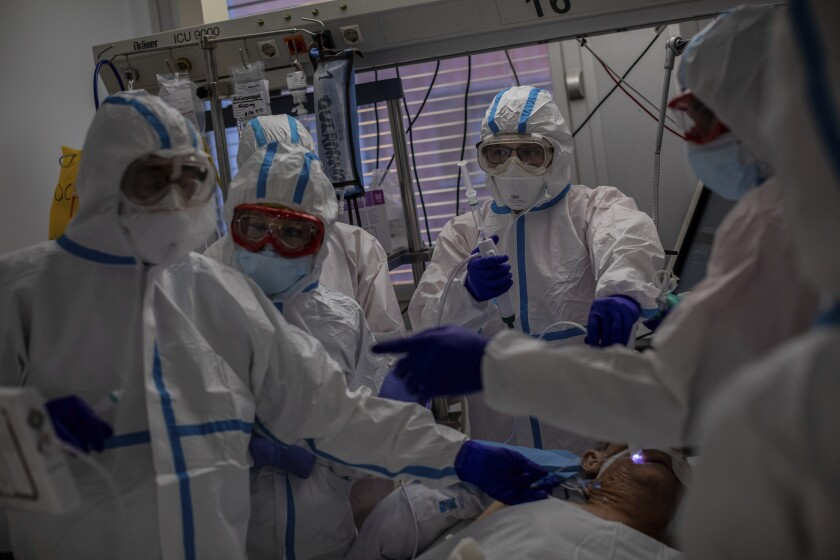FILE - In this Oct. 9, 2020, file photo, a medical team treats a patient infected with COVID-19 in one of the intensive care units (ICU) at the Severo Ochoa hospital in Leganes, outskirts of Madrid, Spain. Europe's second wave of coronavirus infections has struck well before flu season even started. Intensive care wards are filling up again and bars are shutting down. (AP Photo/Bernat Armangue, File)