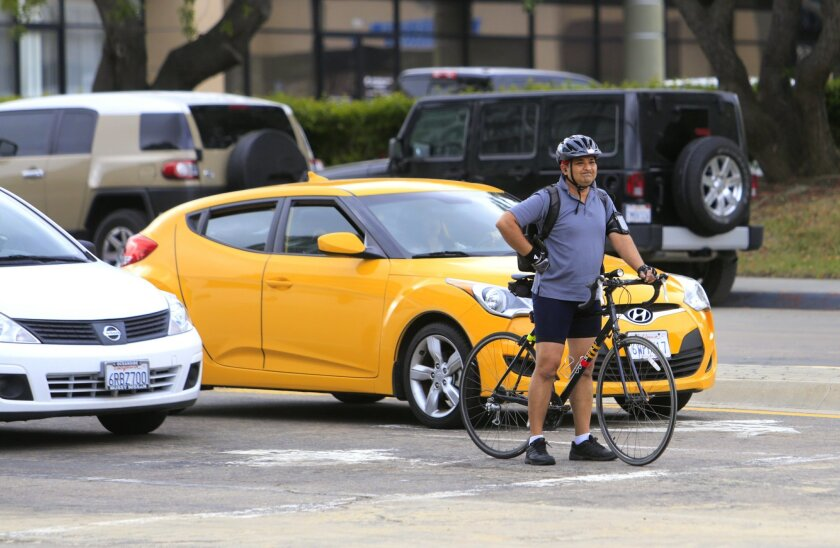 A bicyclist waits for the traffic light change on Mira Mesa Boulevard during Bike to Work Day 2016.