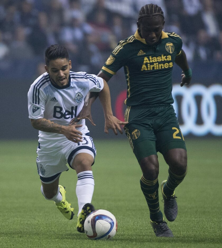 Vancouver Whitecaps FC Cristian Techera (13) fights for control of the ball with Diego Chara (21) of the Portland Timbers during the first half of MLS soccer action in Vancouver, British Columbia, Canada, Sunday, Nov. 8, 2015. (Jonathan Hayward/The Canadian Press via AP)