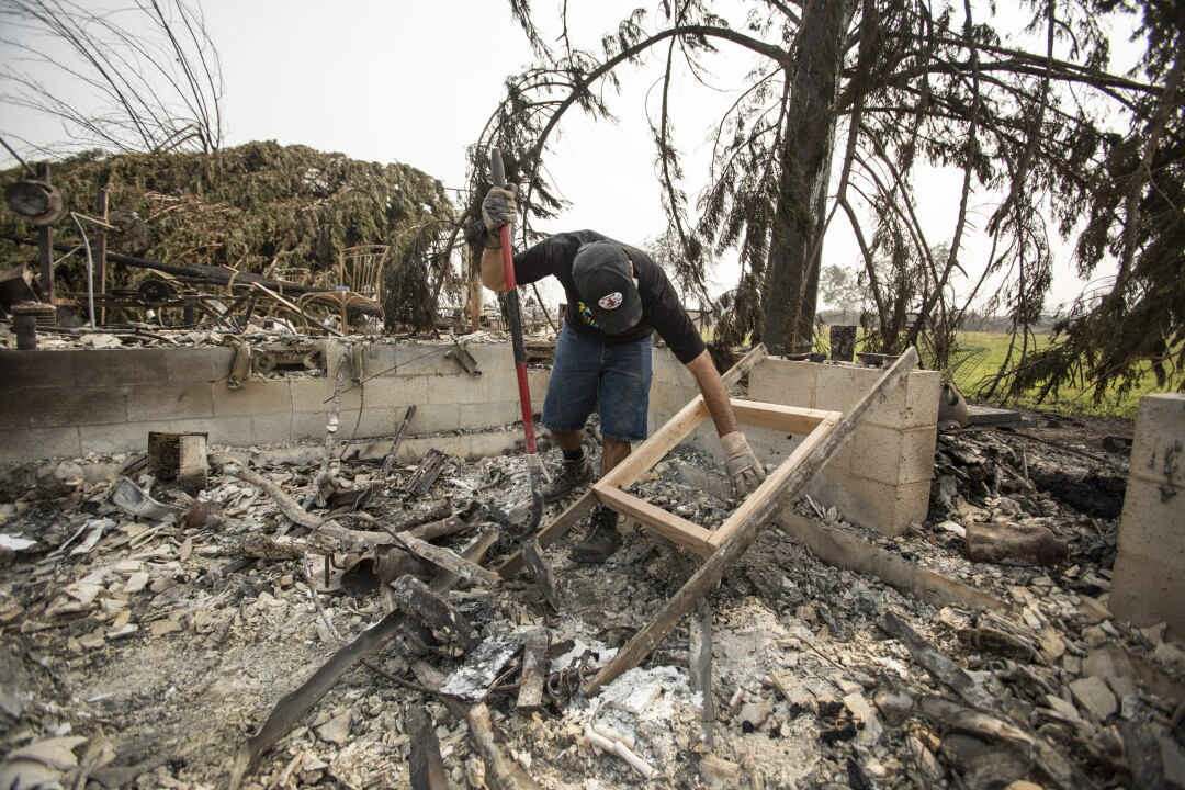 Fred Skaff, 52, of Phoenix, Ore., sifts through the remains of his home, looking for his wedding.
