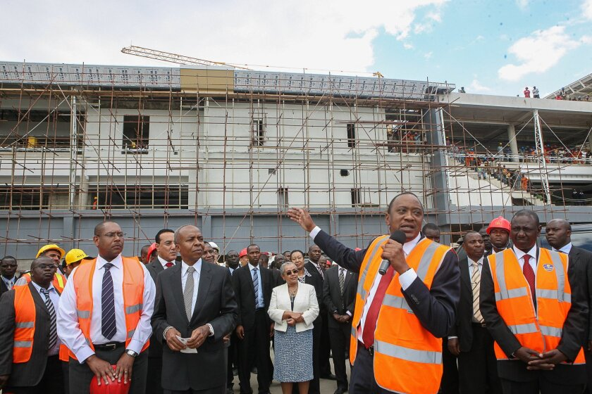 President Uhuru Kenyatta, second right, talks to the construction workers who gathered to welcome him at the Jomo Kenyatta International Airport (JKIA) expansion project in Nairobi, Kenya, Tuesday, Dec. 3, 2013. Only four months after a raging fire engulfed the arrivals terminal at Kenya's main airport, officials are breaking ground on the dlrs 635 million airport terminal in a three year construction project that Kenyan leaders hope will cement the country as East Africa's transportation leader. (AP Photo/ Kenya Presidentail Press Services-HO)