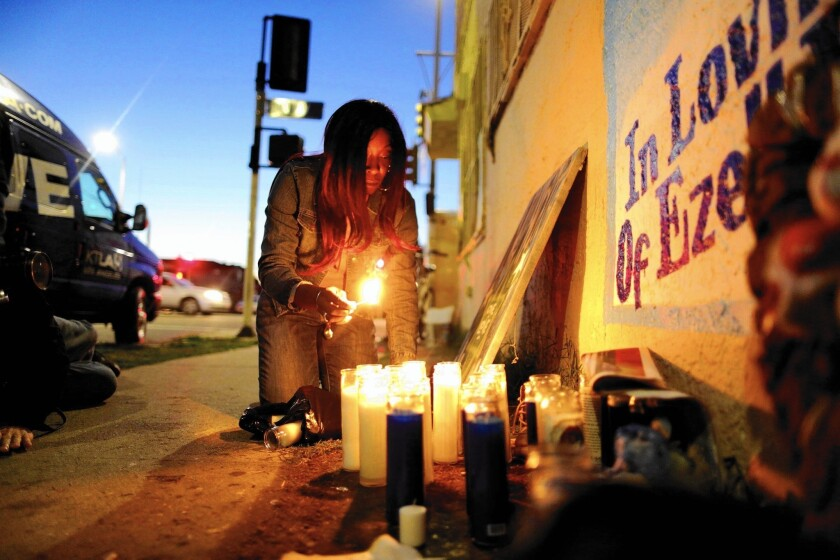 Tritobia Ford, mother of Ezell Ford, lights candles at her slain son's memorial at 65th Street and Broadway.