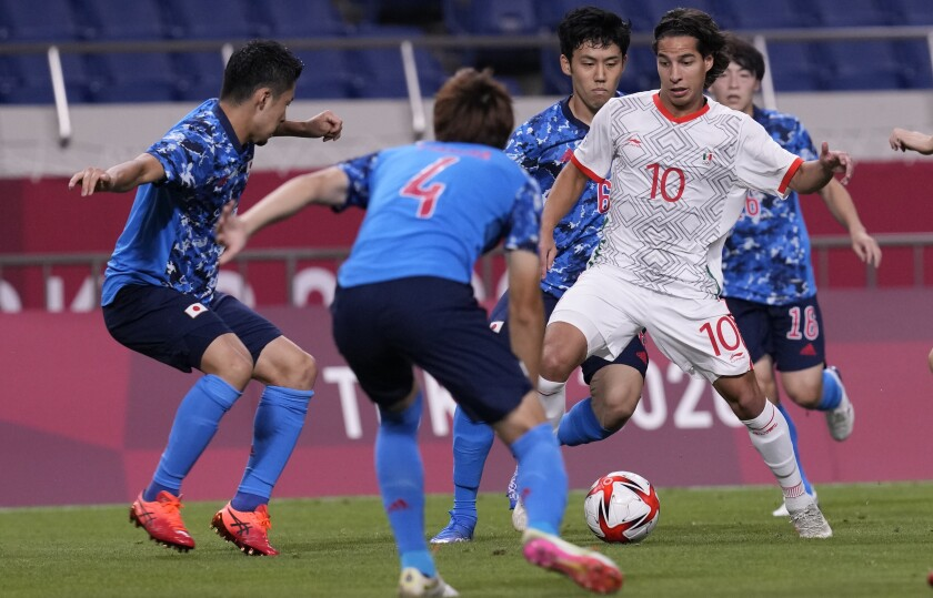 Mexico's Diego Lainez is challenged by Japanese players. (AP Photo/Martin Mejia)