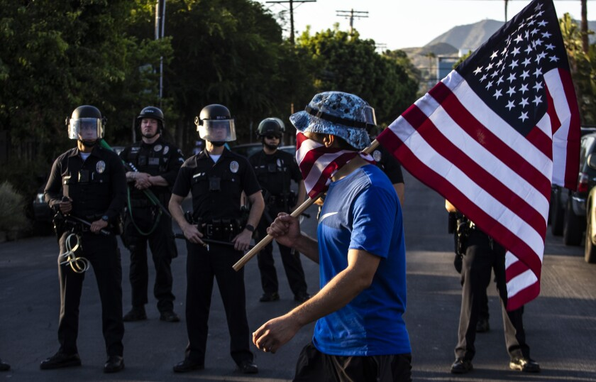A protester carries an American flag past a line of police officers in Hollywood
