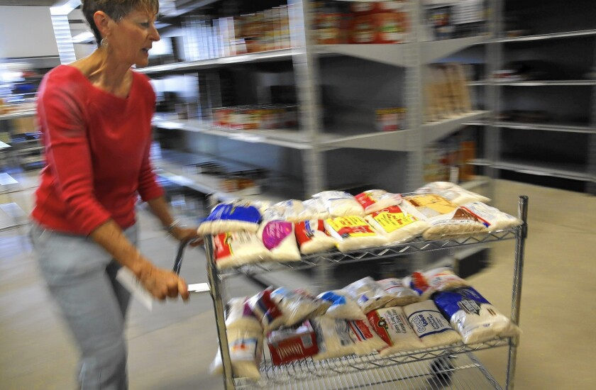 Volunteer Lani Orr pushes a cart of rice at the Families Forward pantry in Irvine in 2013. Orange County has a public-private partnership for reducing food waste from restaurants and other businesses.