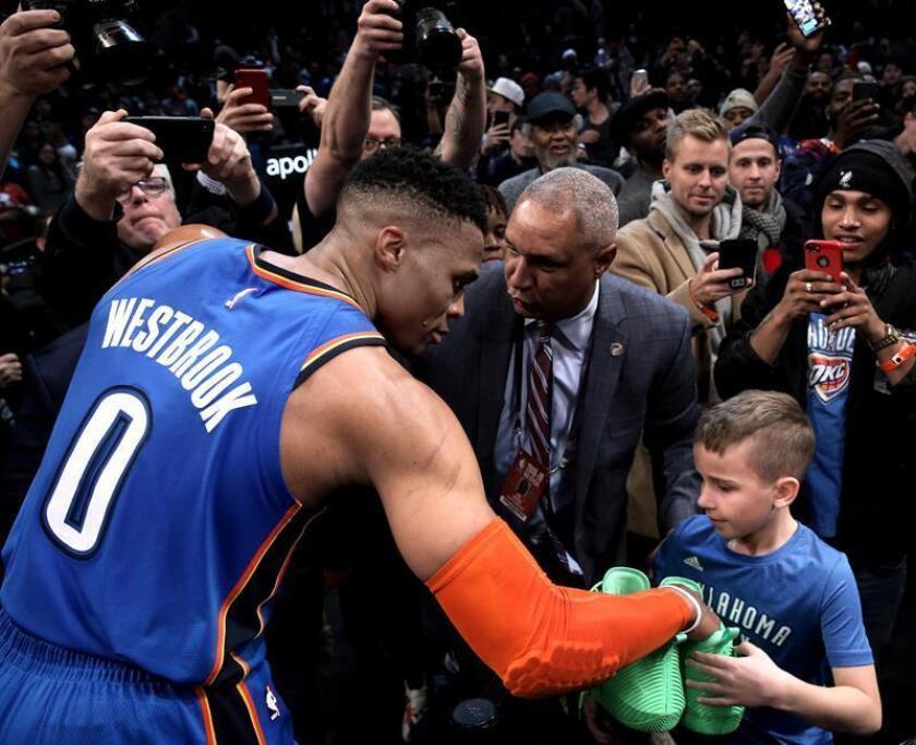El jugador Russell Westbrook (i) de Oklahoma City Thunder le entrega sus zapatos a un aficionado al final del partido de la NBA entre Oklahoma City Thunder y Brooklyn Nets disputado este miércoles en el Barclays Center en Brooklyn, Nueva York (Estados Unidos). EFE