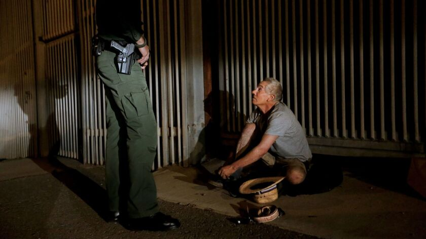 U.S. Border Patrol agent Eduardo Olmos, 38, apprehends a 54-year-old man from Guerrero, Mexico, who had been trying to climb the secondary fence at Border Field State Park into San Diego from Tijuana.