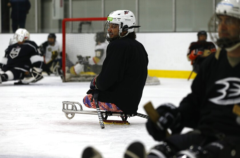 Ralph DeQuebec, a Paralympic hockey gold medalist from Harbor City, coaches players during a sled hockey clinic at Great Park Ice rinks in Irvine on Saturday.