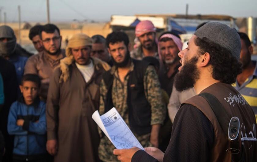 """Un miembro del grupo Estado Islámico conocido como """"Hisba"""", derecha, lee un veredicto dictado por un tribunal islámico en la ciudad de Al Raqa, Siria.(Sitio Extremista via AP, archivo)"""