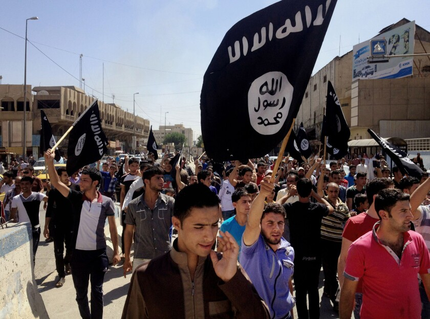 Pro-Islamic State demonstrators march in front of the provincial government headquarters in Mosul in June. Militants in the Iraqi city killed a human rights lawyer because of Facebook posts critical of the group, the United Nations says.