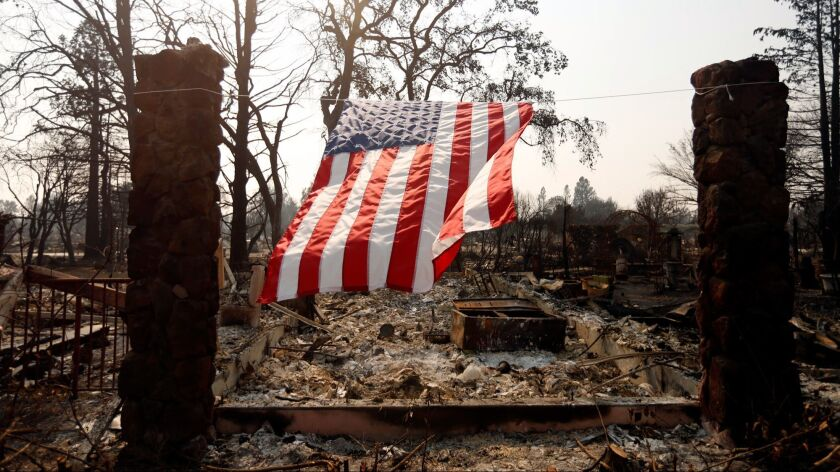 SANTA ROSA, CA -- OCTOBER 18, 2017 -- An American flag hangs from the remnants of a fire ravaged hom