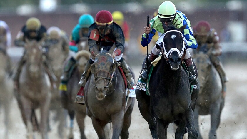 Jockey John Velazquez celebrates as he guides Always Dreaming across the finish line to win the 143rd running of the Kentucky Derby at Churchill Downs on Saturday.