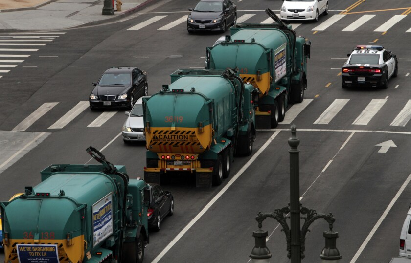 A convoy of garbage trucks participates in a July protest organized by L.A. unions.