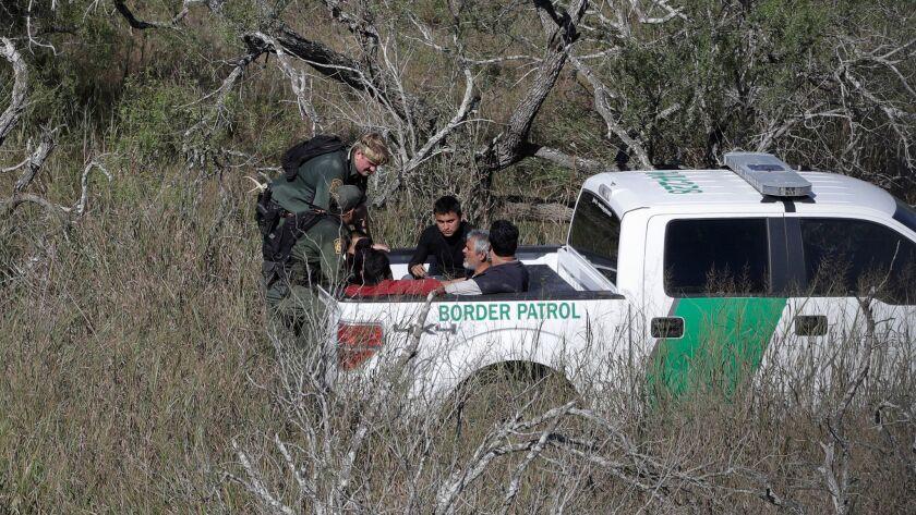 Border Patrol agents stop people suspected of illegally entering the U.S. through a ranch near Edinburg, Texas.