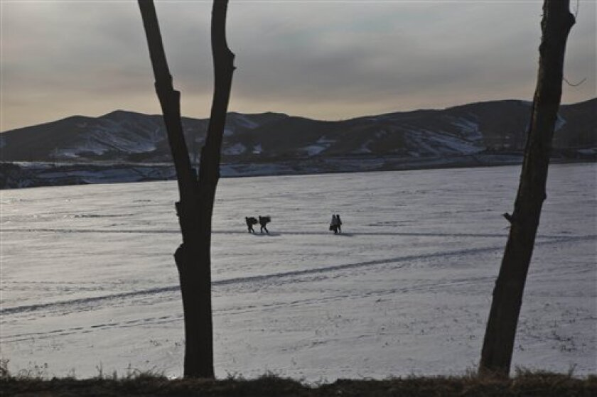 North Koreans carry bundles on their backs as they cross a frozen lake north of the capital city of Pyongyang, North Korea on Sunday, Feb. 24, 2013. (AP Photo/David Guttenfelder)