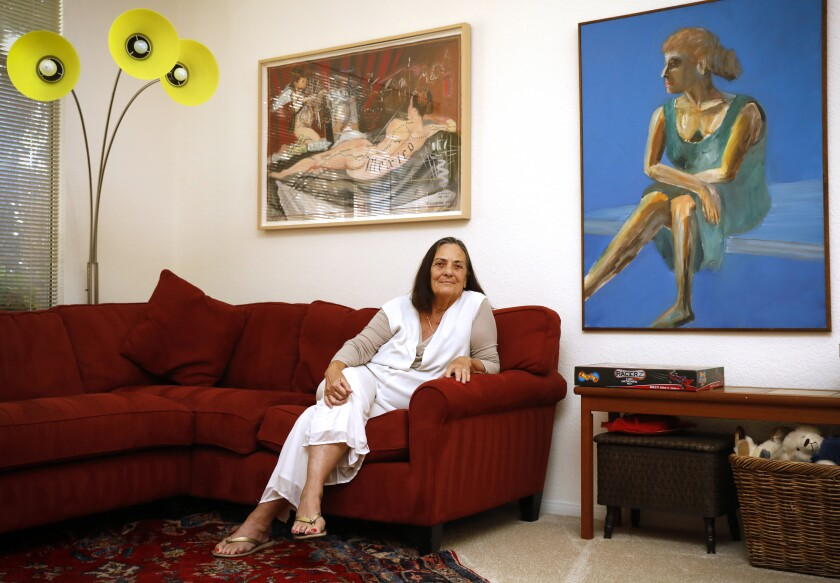 Jean Isaacs sitting on a couch underneath two oversized paintings