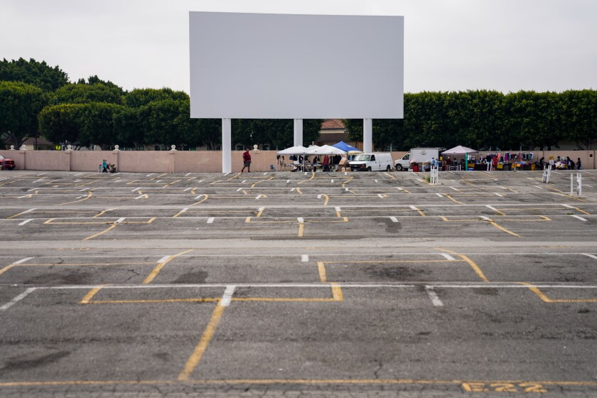 A few cars and vendor booths sit under the drive-in movie screen on a mostly empty parking lot at the Paramount Swap Meet