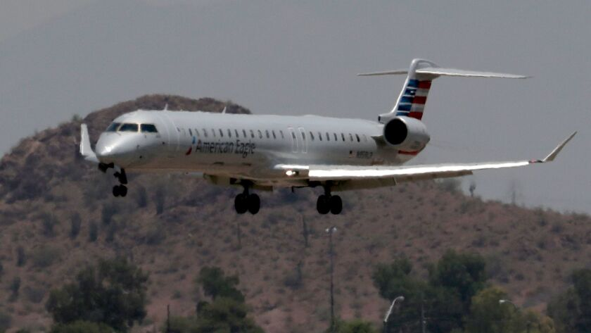 An American Eagle jet flies through heat ripples as it lands at Sky Harbor International Airport in Phoenix. Some employees of Envoy Air, an American Airlines subsidiary that operates under the American Eagle brand, say they must turn to public assistance to make ends meet.