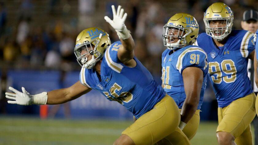 PASADENA, CALIF. - SEP. 3, 2017. UCLA defenders Jaelen Philips, left, Jacob Tuioti-Mariner and Matt