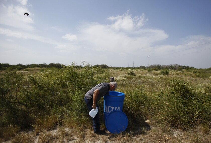 Eddie Canales of the South Texas Human Rights Center, prepares a water dispenser for immigrants walking across the scorching scrublands of southern Texas.