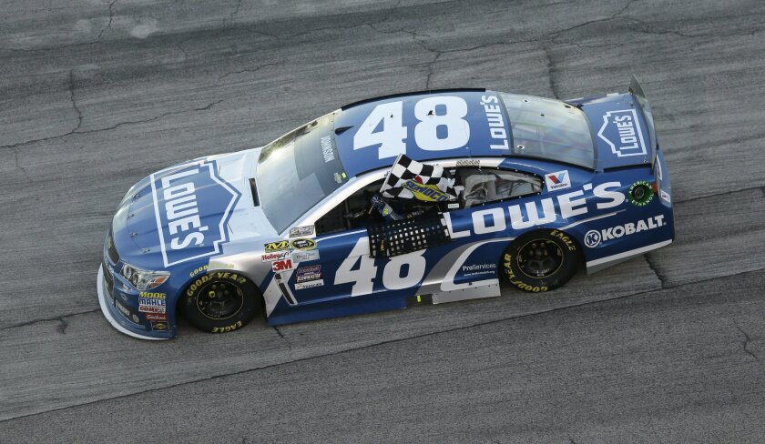 Jimmie Johnson (48) drives with the checked flag after winning the NASCAR Sprit Cup Series auto race at Texas Motor Speedway in Fort Worth, Texas, Sunday, Nov. 8, 2015. (AP Photo/Tim Sharp)
