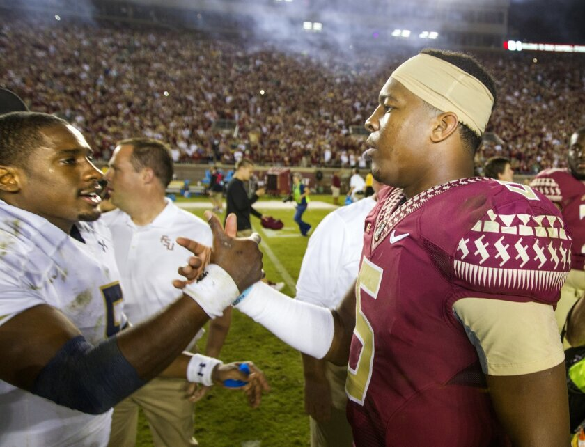 FILE - In this Oct. 18, 2014, file photo, Florida State quarterback Jameis Winston, right, greets Notre Dame quarterback Everett Golson after Florida State won 31-27 in an NCAA college football game in Tallahassee, Fla. Former Notre Dame quarterback Everett Golson says he is transferring to Florida State, where he will have the chance to replace Jameis Winston. In a statement to Fox Sports, Golson said Tuesday, May 19, 2015, after much consideration he will spend his fifth year of eligibility with the Seminoles. (AP Photo/Mark Wallheiser, File)