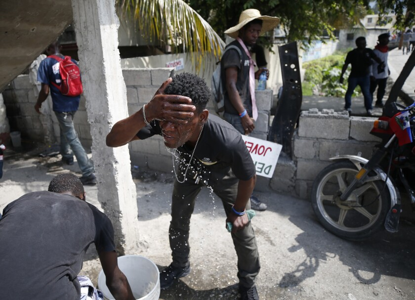 A demonstrator washes his faces from the effects of tear gas during a protest demanding the resignation of President Jovenel Moise, in Port-au-Prince, Haiti, Friday, Oct. 4, 2019. After a two-day respite from the recent protests that have wracked Haiti's capital, opposition leaders urged citizens angry over corruption, gas shortages, and inflation to join them for a massive protest march to the local headquarters of the United Nations. (AP Photo/Rebecca Blackwell)