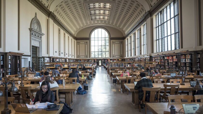 Students read in the main library at UC Berkeley. With its rows and rows of books, the setting is a