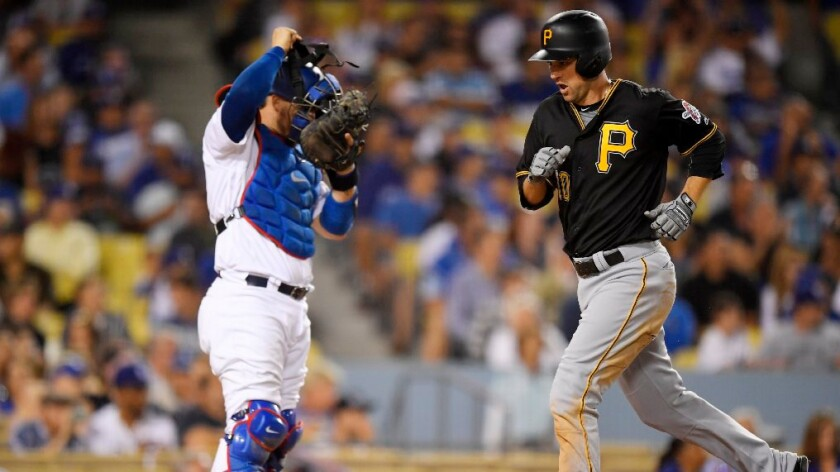 Pirates infielder Jordy Mercer scores on his solo home run as Dodgers catcher Yasmani Grandal stands at the plate during the seventh inning of a game on Aug. 12.