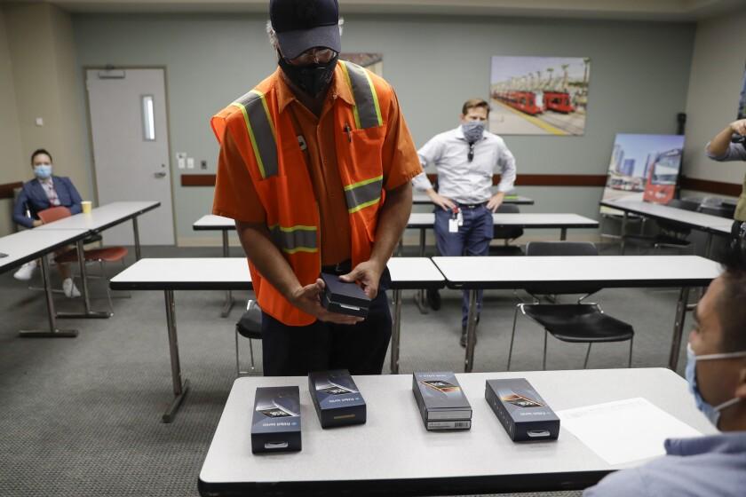San Diego Metropolitan Transit System worker John Freeland receives a new Fitbit device