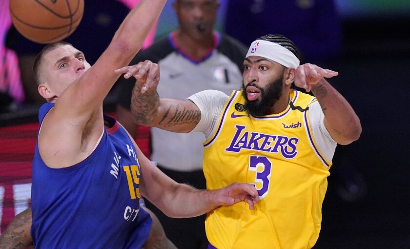 Denver Nuggets center Nikola Jokic (15) defends against a pass by Los Angeles Lakers' Anthony Davis.
