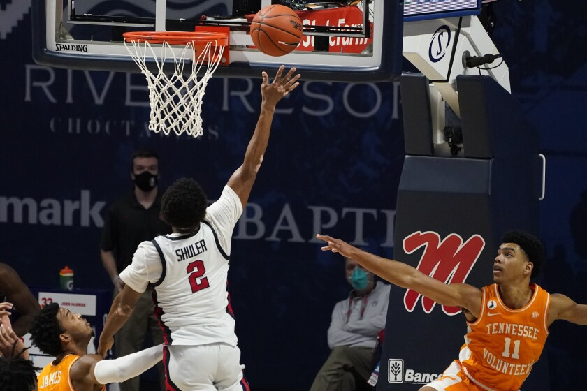 Mississippi guard Devontae Shuler (2) splits Tennessee defenders including guard Jaden Springer (11) as he makes a layup during the second half of an NCAA college basketball game in Oxford, Miss., Tuesday, Feb. 2, 2021. Mississippi won 52-50. (AP Photo/Rogelio V. Solis)