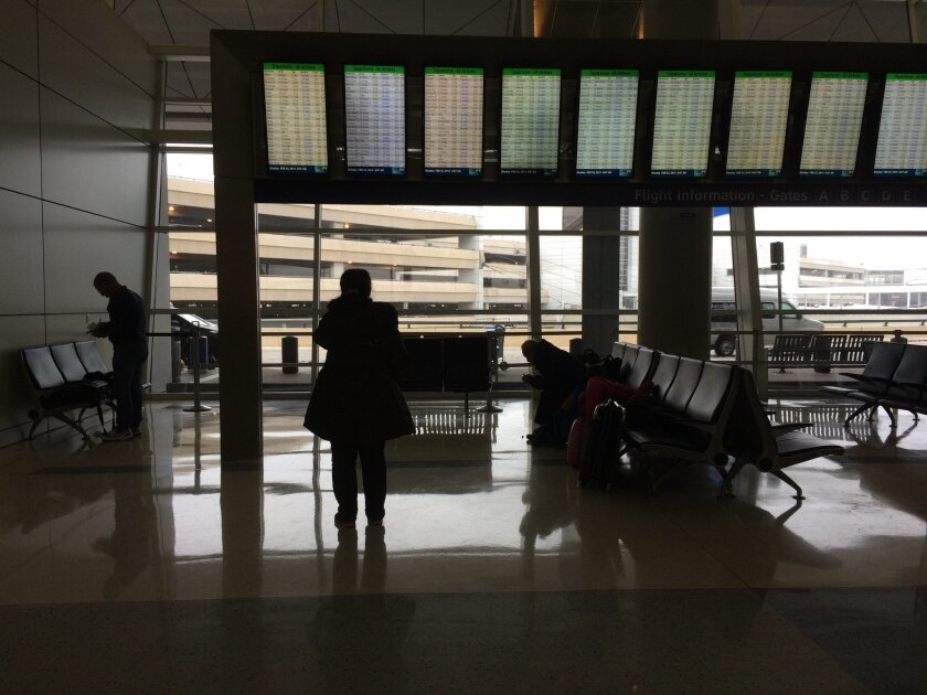 In a precursor of weekend delays, a traveler on Monday reads a flight tracking board showing numerous cancellations at Dallas-Fort Worth International Airport.