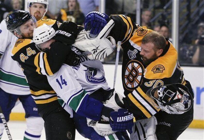 Boston Bruins goalie Tim Thomas (30) takes a shot at Vancouver Canucks left wing Alex Burrows (14) as Boston Bruins defenseman Dennis Seidenberg (44) pulls Burrows back late in the game during Game 4 of the NHL hockey Stanley Cup finals, Wednesday, June 8, 2011, in Boston. (AP Photo/Elise Amendola)