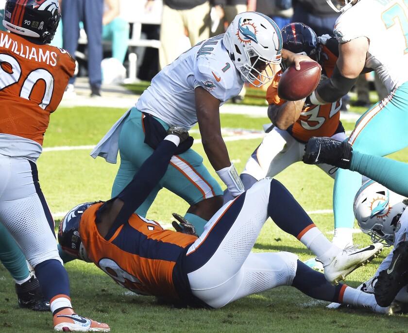 Denver Broncos linebacker Malik Reed, bottom, sacks Miami Dolphins quarterback Tua Tagovailoa, top, in the first half of an NFL football game in Denver, Sunday, Nov. 22, 2020. (Jerilee Bennett/The Gazette via AP)