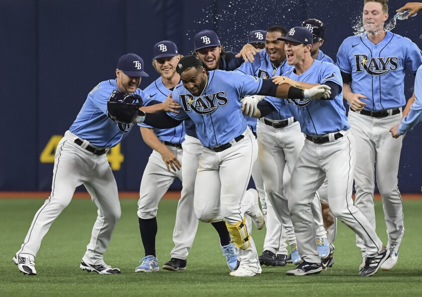 Tampa Bay Rays teammates celebrate with Yandy Diaz, center, after Randy Arozarena scored from third base on Diaz's fielder's choice to Cleveland Indians second baseman Cesar Hernandez during the ninth inning of a baseball game Monday, July 5, 2021, in St. Petersburg, Fla. (AP Photo/Steve Nesius)