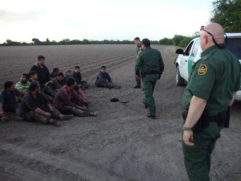 Border Patrol division chief Robert Duff, right, and other agents round up migrants in the Rio Grande Valley.