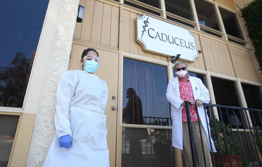 Dr. Gregg DeNicola and assistant Janet Muratalla wait to administer drive-up coronavirus testing outside the Caduceus Medical Group office in Laguna Beach.