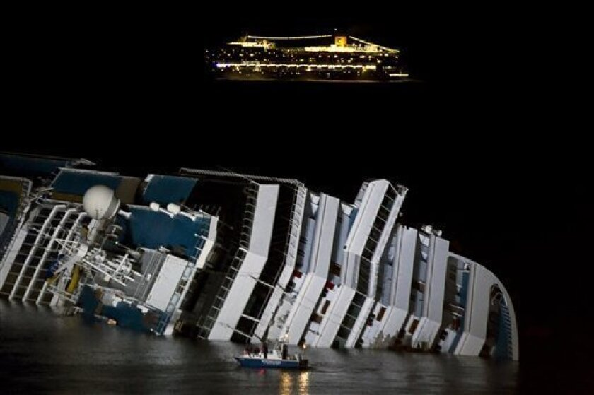 The cruise ship Costa Serena passes offshore as its sister ship Costa Concordia lies on its side off the tiny Tuscan island of Giglio, Italy, Wednesday, Jan. 18, 2012. The $450 million Costa Concordia cruise ship was carrying more than 4,200 passengers and crew when it slammed into a reef Friday of
