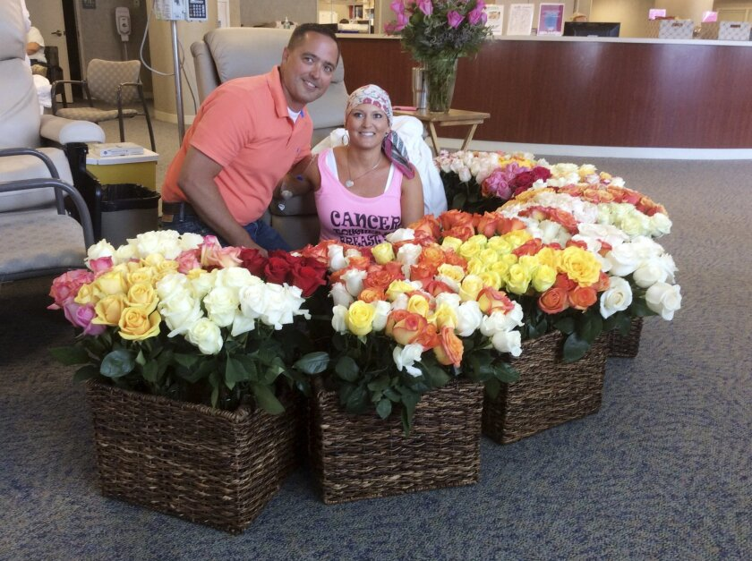 This June 23, 2016 photo provided by Brad Bousquet shows Bousquet with his wife, Alissa, and the 500 roses he presented to her at the Methodist Estabrook Cancer Center in Omaha, Neb., to celebrate her last chemotherapy treatment. Brad writes that he secretly texted wife Alissa's friends and family
