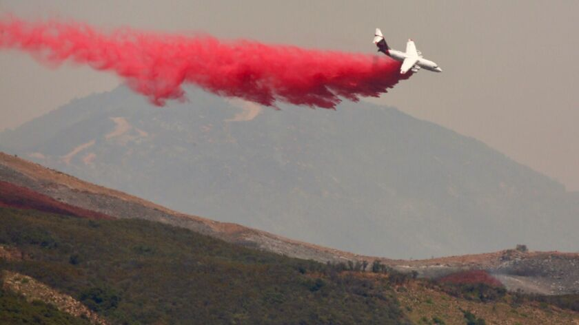 A plane drops fire retardant on the Whittier fire in Goleta on Saturday as firefighters on the ground employed controlled backfires along Camino Cielo in the Santa Ynez Mountains.